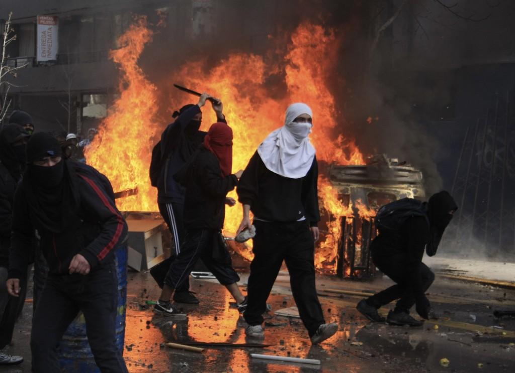 Encapuchados levantan barricadas durante disturbios producidos en una marcha de estudiantes y maestros contra el gobierno en Santiago, Chile, el martes 9 de agosto de 2011. s. (AP Photo/Sebastian Silva)