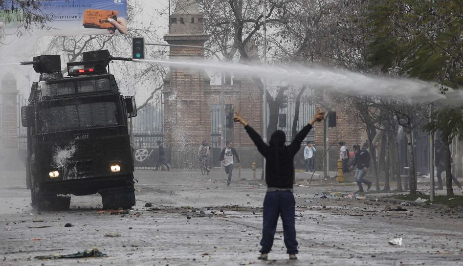 A student protester throws up his arms in front of a riot police water cannon during a demonstration against the government, to demand changes in the public state education system in Santiago August 28, 2012. Chilean students have been protesting against what they say is profiteering in the state education system.  REUTERS/Ivan Alvarado (CHILE - Tags: POLITICS CIVIL UNREST EDUCATION)